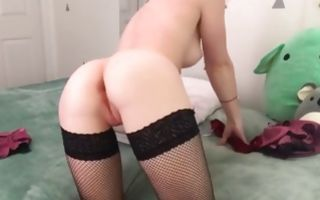 Seductive babe in her stockings fingers pussy on the bed